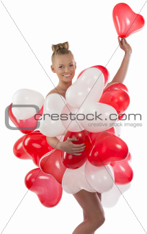blonde girl with many balloons on her body takes one balloon