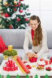 Happy young woman preparing Christmas gift