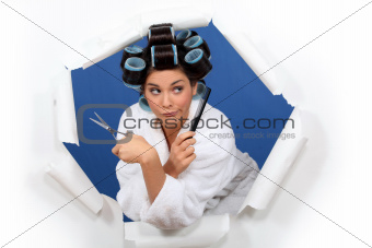 Funny girl with hair curlers, scissors and a comb
