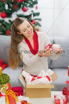 Happy young woman packing Christmas present parcel