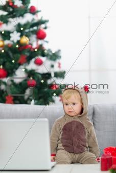 Baby in Christmas deer costume near Christmas tree looking in laptop