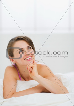 Portrait of thoughtful girl laying on bed