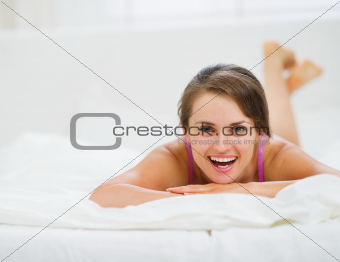 Portrait of happy young woman laying on bed