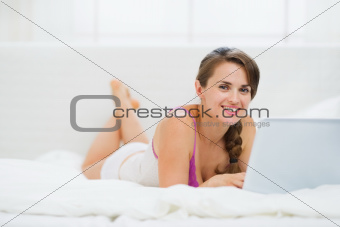 Happy young woman laying on bed and surfing internet