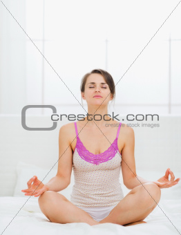 Young woman making yoga on bed