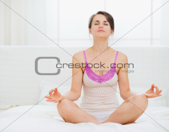 Young woman sitting in yoga pose on bed