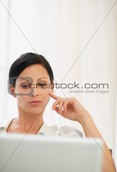 Portrait of thoughtful young woman working on laptop