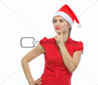 Portrait of thinking young woman in Santa hat looking on copy space
