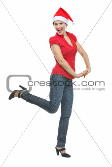Cheerful young woman in Santa hat dancing
