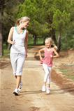 Mother and daughter running in park
