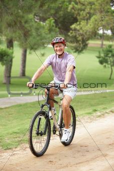 Senior man enjoying bike ride in park
