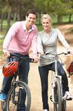 Couple riding bicycle in park