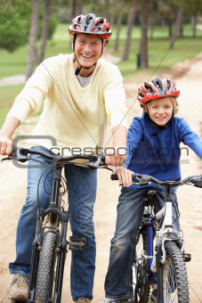 Grandfather and grandson riding bicycle in park
