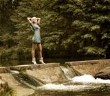 Beautiful Blonde Woman Standing near the Waterfall