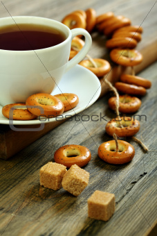 Cup of tea and small bagels with poppy seeds.