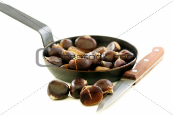 Knife and the chestnuts in a pan.