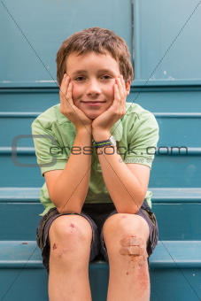 Young boy with scrapped knees and band aids