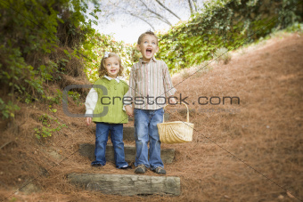 Adorable Brother and Sister Children Holding Hands Walking Down Wood Steps with Basket Outside.