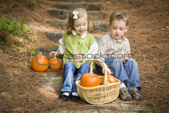 Cute Young Brother and Sister Children Sitting on Wood Steps Laughing with Pumpkins in a Basket.