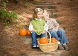 Adorable Brother and Sister Children Sitting on Wood Steps with Pumpkins Whispering Secrets or Kissing Cheek.