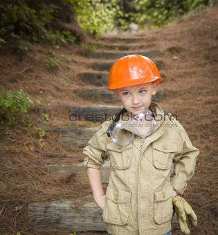 Happy Adorable Child Boy with Big Gloves, Hard Hat and Goggles Playing Handyman Outside.