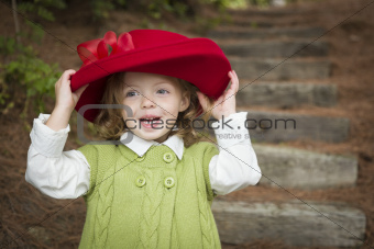 Happy Adorable Child Girl with Red Hat Playing Outside.