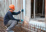 Construction worker cutting steel rods