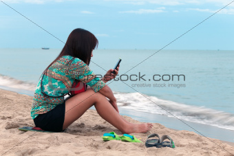 Asian woman sit on the beach.