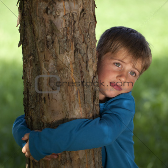 Little boy embracing a tree