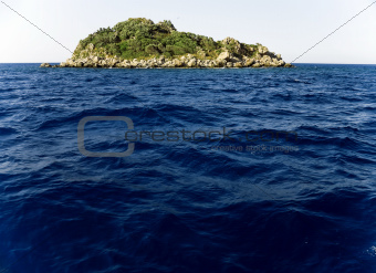green island in the middle of the ocean waves on blue sky background