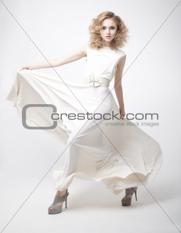 Attractive beautiful young blond hair girl in white dress