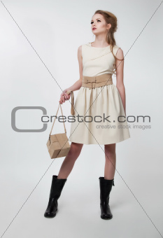 Pretty young girl in modern dress with purse on podium