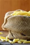 Linen bag of pasta (penne) on a wooden table