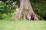 Three happy female friends sitting near big tree