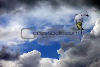 Freestyle ski jumper with crossed skis against cloudy sky