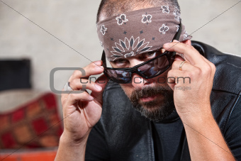 Intimidating male biker in bandana looking over his sunglasses