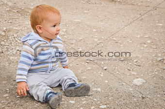 A child sitting on a background a bank