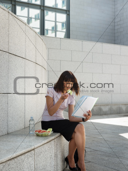 business person eating lunch outside office and reading papers