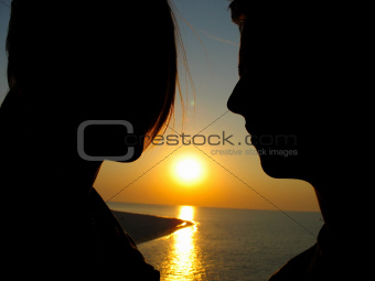Silhouette of romantic young couple at sea sunset