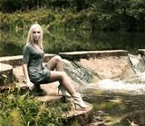 Beautiful Blonde Woman Sitting near the Waterfall