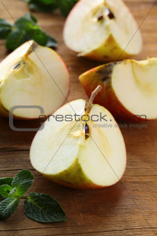 ripe red apples cut on a wooden board