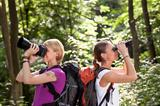 two women hiking in forest and looking with binoculars