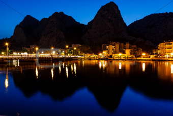 Mountain Silhouettes and Illuminated Town of Omis Reflecting in