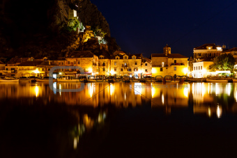 Illuminated Pirate Castle and Town of Omis Reflecting in the Cet