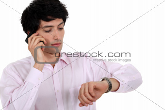 man talking on his cell and watching his watch