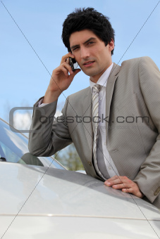 Annoyed businessman talking on his mobile phone by his car