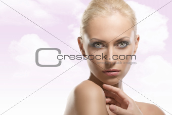beauty portrait of blonde girl, her hand is near the neck