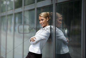confident woman leaning on office building window
