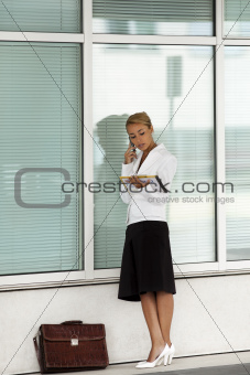 woman holding file speaking on telephone near office building