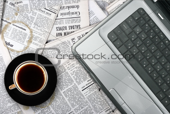 workplace with laptop and coffee cup on newspaper background
